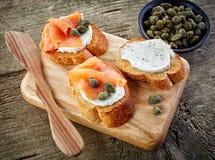 Fette tostate del pane con formaggio cremoso ed il salmone affumicato fotografia stock libera da diritti