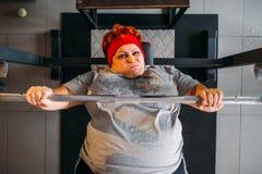 Fette verschwitzte Frau, Training mit Barbell in der Turnhalle stockfotografie