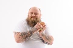 Fetter Fleisch fressender Cheeseburger mit Genuss Lizenzfreies Stockfoto