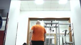 Fetter gut aussehender Mann in einer Turnhalle im orange T-Shirt kommt stock video footage
