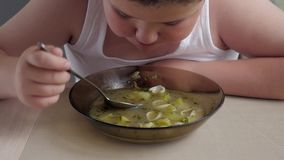 Fetter Kinderjunge mit Appetit isst Suppe in der Küche, beleibte Kinder des Konzeptes stock video