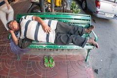 Fetter Mann, der auf einer Bank schläft Stockfotos