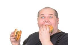 Fetter Mann, der gierig Hamburger isst Stockfotos