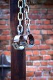Fetters, manacles on brick background. Old fetters, manacles brick two old rusted iron rings on wall background Royalty Free Stock Photo