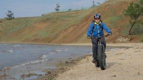 Fettes Fahrrad nannte auch fatbike oder Fettreifenfahrrad im Sommer, der auf den Strand fährt stock video