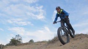 Fettes Fahrrad nannte auch fatbike oder Fettreifenfahrrad im Sommerreiten im Sandhügel stock video