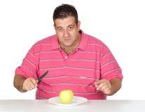 Fettes Fleisch fressendes ein Apfel Stockfotografie