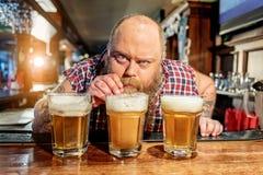 Fettes männliches Probierenalkoholgetränk im dramshop Lizenzfreie Stockbilder