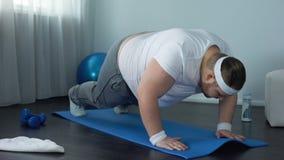 Fettes männliches Versuchen zu tun, Übung zu Hause hochzudrücken, schwache Muskeln, Mangel an Motivation stock video
