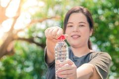 Fettig asiatisk vit flaska för rent vatten för flickahåll royaltyfri bild