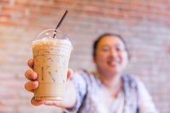 Fettiga asiatiska kvinnor ler med kall is mjölkar kaffedrinken arkivfoto
