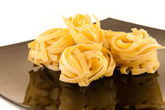 Fettuccine. Uncooked f fettuccine on brown plate isolated royalty free stock image