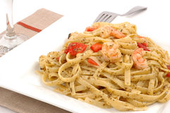 Fettuccine. Delicious fettuccine with pesto roasted peppers and shrimp royalty free stock image