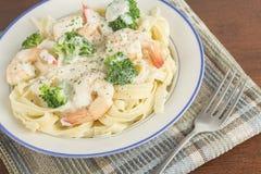 Fettuccine Alfredo Shrimp. Italian health conscious fettuccine alfredo shrimp with broccoli florets Royalty Free Stock Photography