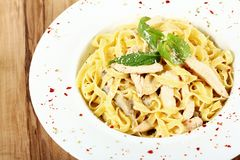Fettuccine Alfredo on wooden table stock photography