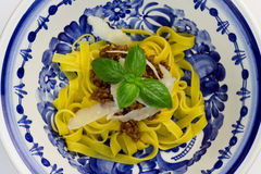 Fettuccine bolognese. Fettuccine pasta with bolognese sauce, sprinkled with shaved parmesan and decorated with basil royalty free stock photography