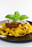 Fettuccine bolognese. Fettuccine pasta with bolognese sauce, sprinkled with shaved parmesan and decorated with basil royalty free stock images