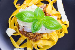Fettuccine bolognese. Fettuccine pasta with bolognese sauce, sprinkled with shaved parmesan and decorated with basil stock images