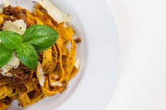 Fettuccine bolognese. Fettuccine pasta with bolognese sauce, sprinkled with shaved parmesan and decorated with basil royalty free stock image
