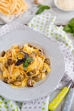 Fettuccine carbonara in a bowl. Garnished with quail egg, mushrooms and basil Royalty Free Stock Images