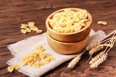 Fettuccine crudo della pasta in una ciotola di legno Fotografie Stock Libere da Diritti