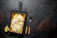 Fettuccine della pasta con la salsa di Carbonara nel piatto e nelle fette di limone immagine stock libera da diritti
