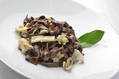 Fettuccine för pastamaträttchoklad med räkor och bläckfisken Arkivfoto