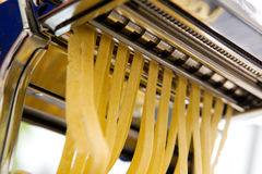 Fettuccine fresh. Fettuccine coming out of a manual pasta machine - shallow depth of field with focus on the pasta stock photography