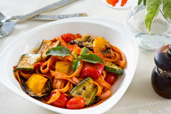 Fettuccine and Grilled vegetables in tomato sauce. Basil on top Royalty Free Stock Photos