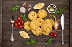 Fettuccine with ingredients for cooking pasta on wooden backgrou Stock Photo