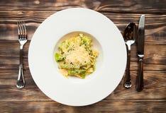 Fettuccine italiano con las habas verdes y el parmesano en un woode oscuro Foto de archivo