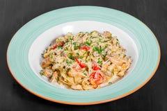 Fettuccine makaron z kurczaka mięsem, pomidorem, pieczarkami, serowym kumberlandem i zieleniami na talerzu, fotografia stock