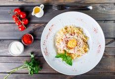 Fettuccine makaron z mięsem, baleronem, jajkiem, parmesan serem, basilem i kremowym kumberlandem na talerzu na ciemnym drewnianym obrazy royalty free