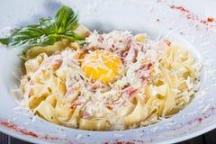 Fettuccine makaron z mięsem, baleronem, jajkiem, parmesan serem, basilem i kremowym kumberlandem na talerzu na ciemnym drewnianym obrazy stock