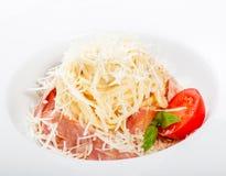 Fettuccine makaron z mięsem, baleronem, parmesan serem, basilem i pomidorem na talerzu na lekkim drewnianym tle, obraz stock