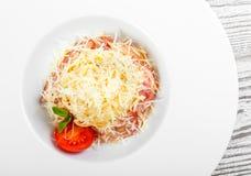 Fettuccine makaron z mięsem, baleronem, parmesan serem, basilem i pomidorem na talerzu na lekkim drewnianym tle, obraz royalty free
