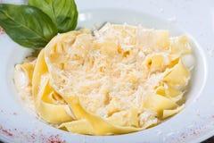Fettuccine makaron z parmesan serem, basilem i kremowym kumberlandem na ciemnym drewnianym tle, zdjęcia royalty free