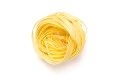Fettuccine neat. One fettuccine pasta nest, isolated on white, view from above royalty free stock images