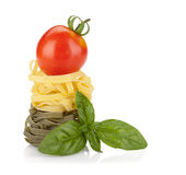 Fettuccine nest pasta with tomato cherry and basil Stock Photography