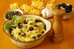 Fettuccine with olives and capers Stock Photos