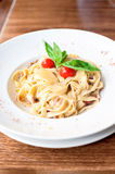 Fettuccine pasta with cream sauce and bacon. Indoors closeup. Royalty Free Stock Image