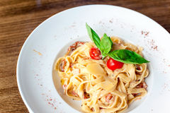 Fettuccine pasta with cream sauce and bacon. Indoors closeup. Royalty Free Stock Photos