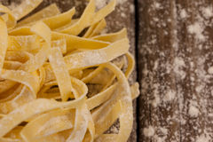 Fettuccine pasta dusted with flour. On wooden table royalty free stock image