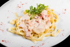 Fettuccine pasta with meat, cream sauce and herbs, in bowl isolated on black background. stock images