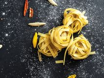 Fettuccine pasta noodles decorated with pieces of red bell pepper and chilly pepper and white flour royalty free stock image
