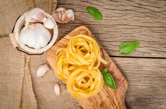 Fettuccine pasta set up on cutting wood. Fettuccine pasta ingred. Ients for Italian food Stock Photo