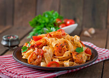 Fettuccine pasta with shrimp. Tomatoes and herbs royalty free stock images