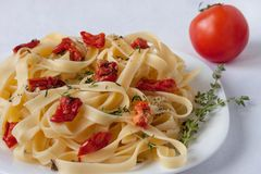 Fettuccine pasta with sun-dried tomatoes and rosemary. Close up stock images