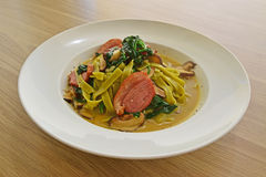 Fettuccine pasta in tasty broth fresh green spinach and slices of smoked duck Royalty Free Stock Image
