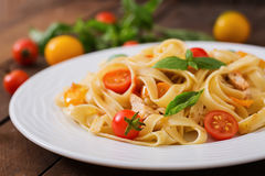 Fettuccine pasta in tomato sauce with chicken, tomatoes decorated with basil Royalty Free Stock Image